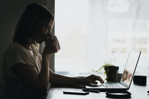 woman sitting in front of laptop while drinking